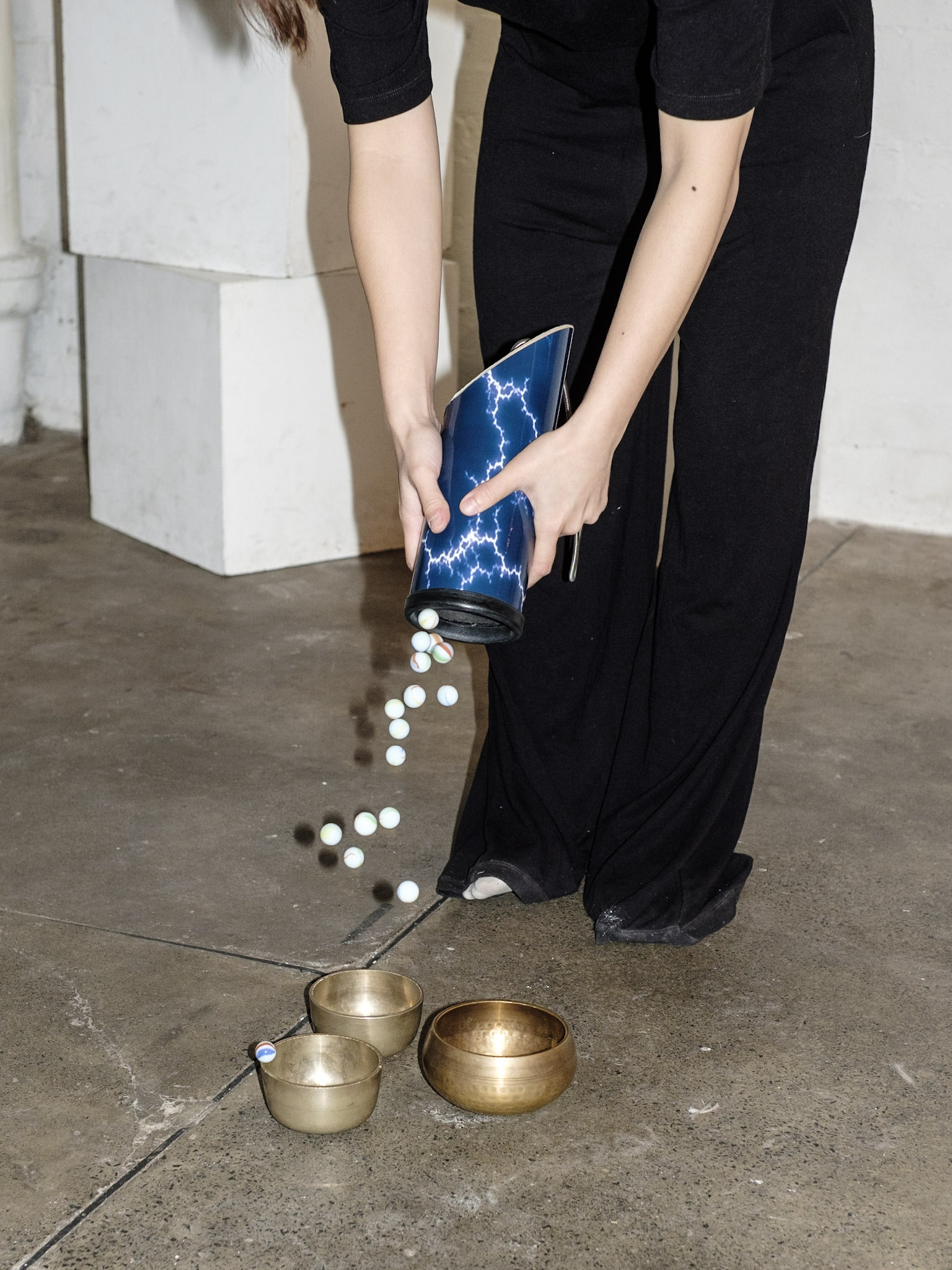 Percussionist Angela Wai-Nok Hui tips marbles onto brass Tibetan bowls in Pale Flower 1 by Zhuosheng Jin